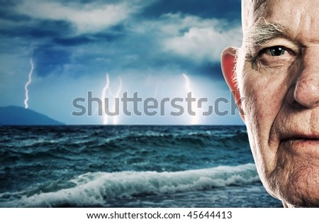 Elderly man's face over stormy ocean background - stock photo