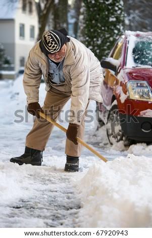 Elderly man shovels snow from sidewalk - stock photo