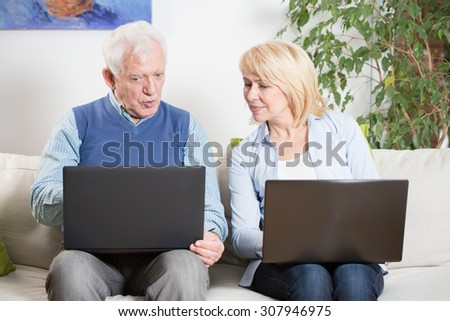 Elderly man showing his wife new application on laptop - stock photo