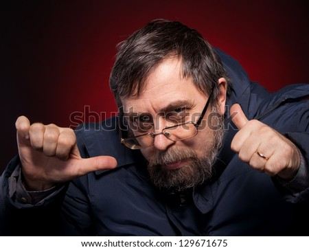 Elderly man shows ok sigh on red background
