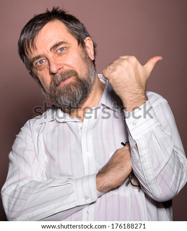 Elderly man shows ok sign on brown background