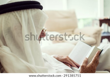 Elderly man sitting and reading book - stock photo