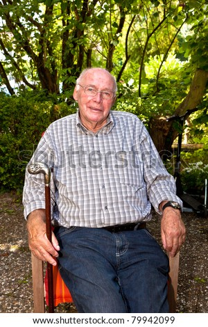elderly man sitting in a chair in his garden and looks very friendly - stock photo