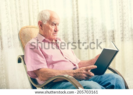 Elderly man sitting on chair reading book at home - stock photo