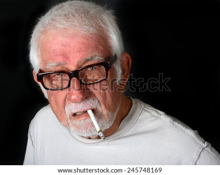 Elderly man smoking a cigarette with an angry and upset look on his face - stock photo