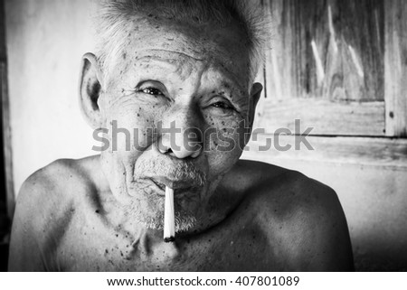 Elderly man smoking ,black and white tone - stock photo