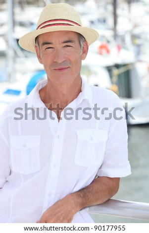 Elderly man stood in front of port - stock photo