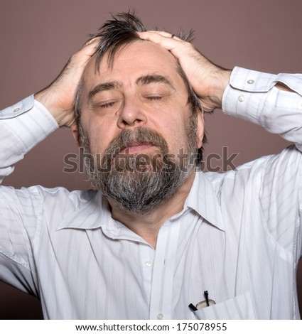 Elderly man suffering from a headache and holding his head by hands.