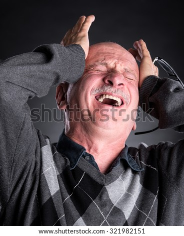 Elderly man suffering from a headache on a  background