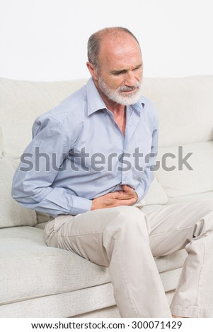 Elderly man suffering from stomachache - stock photo