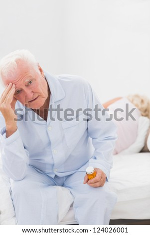Elderly man suffering while woman sleeping on the bed - stock photo