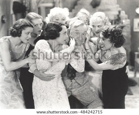 Elderly man surrounded by flirtatous young women
