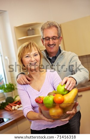 Elderly man taking apple from woman with fruit bowl