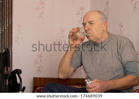 Elderly man taking his medication drinking the tablets down with a glass of water - stock photo
