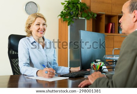 Elderly man talking with bank manager about opening saving account - stock photo