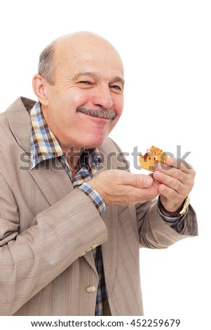 elderly man tries delicious muffin or cupcake