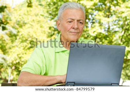 Elderly man using laptop in the park. - stock photo