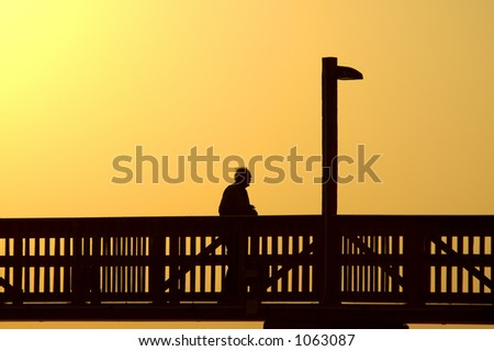 Elderly man walks boardwalk alone at days end