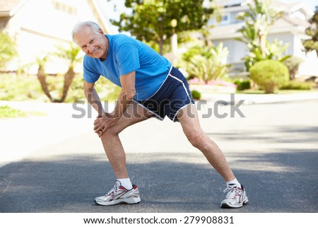 Elderly man warming up for run - stock photo