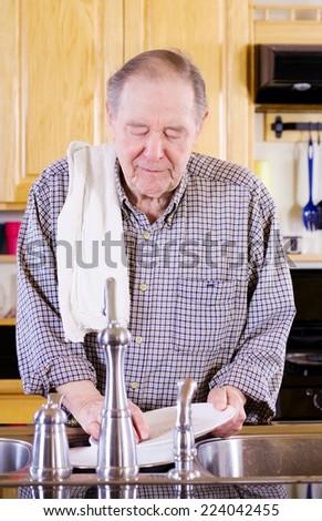 Elderly man washing dishes in kitchen - stock photo