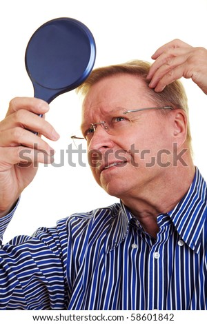 Elderly man watching his receding hair line in mirror - stock photo