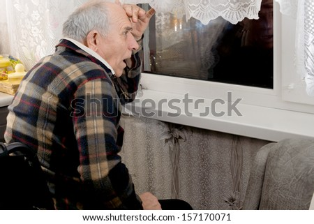 Elderly man watching through a window at night reacting with a look of horror to something that is happening in the darkness - stock photo