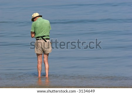 Elderly man wearing a hat and shorts and paddling in the sea.