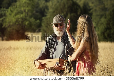 Elderly man with a box in his hands and a young woman in a field - stock photo
