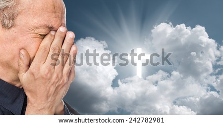 Elderly man with a face closed by hands on the background of the sky with a cross, a symbol of faith - stock photo