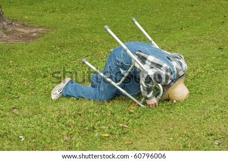 elderly man with a walker takes a tumble in the park - stock photo