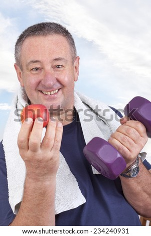 Elderly man with apple and dumbbells - stock photo