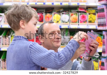 elderly man with boy in shop of seeds - stock photo