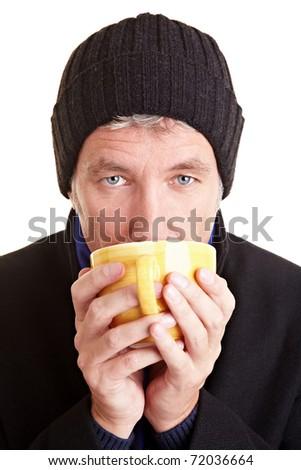 Elderly man with cap drinking coffee in winter - stock photo