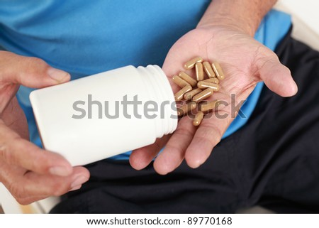 Elderly man with pills or vitamins on his hand - stock photo