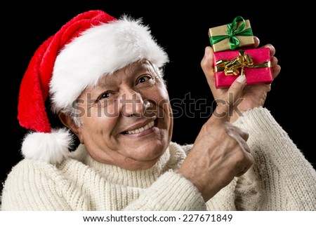 Elderly man with red Santa Claus cap and warm pullover. His raised right index finger is pointing at a red and golden wrapped present held in his left hand above eye-level. Isolated over black. - stock photo