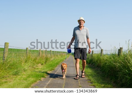 Elderly man with straw hat walking the dog in summer season - stock photo