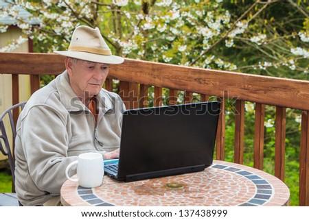Elderly Man Working on Laptop Computer - stock photo