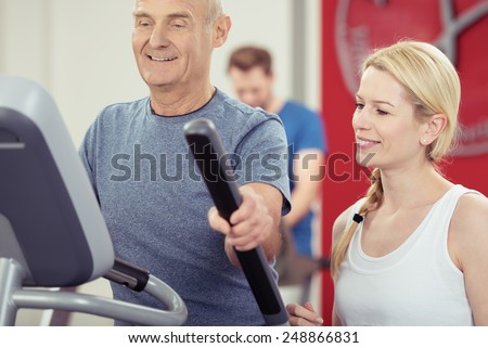 Elderly man working out at a gym monitoring his progress with an attractive young female trainer on the readout on the equipment - stock photo