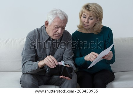 Elderly marriage sitting and discussing their financial problems - stock photo