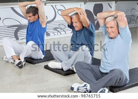 Elderly men stretching in fitness center on gym mats