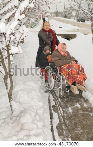Elderly mum the invalid with the daughter on walk in the winter.