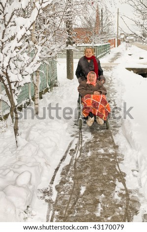 Elderly mum the invalid with the daughter on walk in the winter. - stock photo