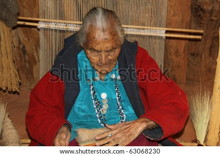 elderly Navajo woman demonstrating weaving of wool in a hogan in monument  valley - stock photo