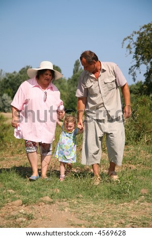 elderly pair goes for a walk with the granddaughter - stock photo
