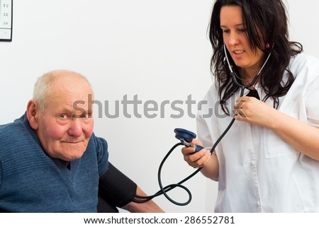Elderly patient at the cardiology - doctor measuring his blood-pressure.  - stock photo