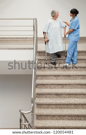 Elderly patient on crutches being helped by nurse to go down stairs - stock photo
