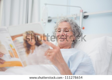 Elderly patient reading a magazine on her bed in hospital ward