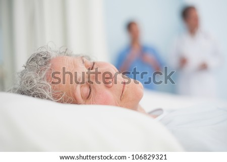 Elderly patient sleeping on a bed next to a doctor in hospital ward