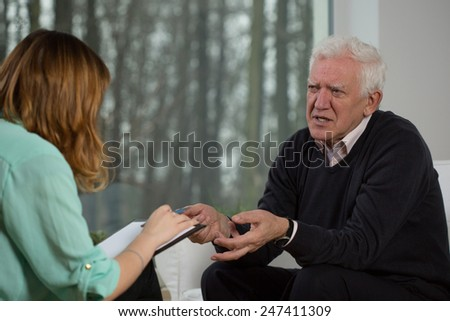 Elderly patient talking with psychotherapist about his troubles - stock photo