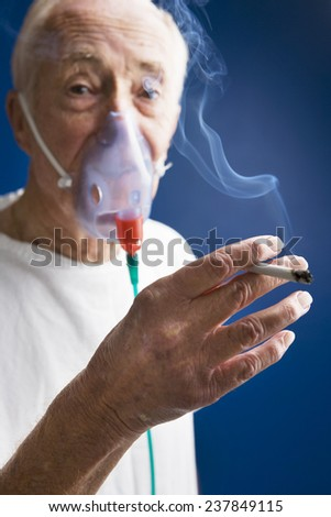 Elderly Patient Wearing Oxygen Mask and Smoking Cigarette - stock photo